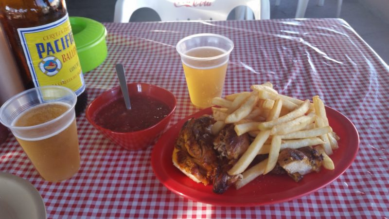 A plate of roast chicken with french fries and beer on a gingham tablecloth.