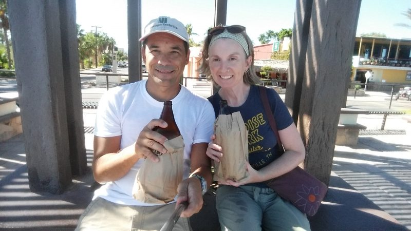 A man and woman drinking bottles of beer out of brown paper bags in a town on the Baja Penisula.
