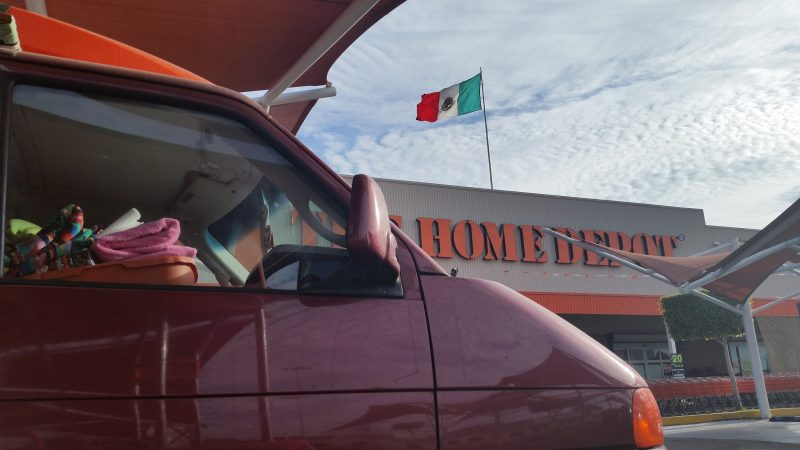A maroon Volkswagen van outside of Home Depot in La Paz, Baja California which has a Mexican flag blowing in the wind on its roof.