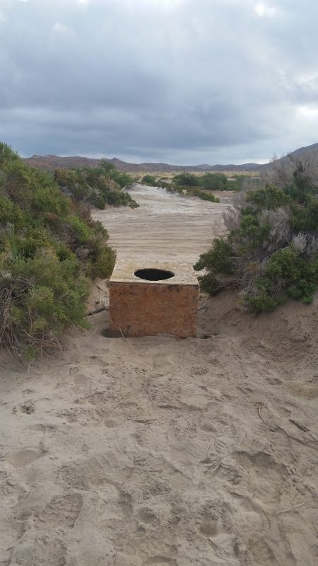 A very basic baja camping toilet on top of a sand dune.