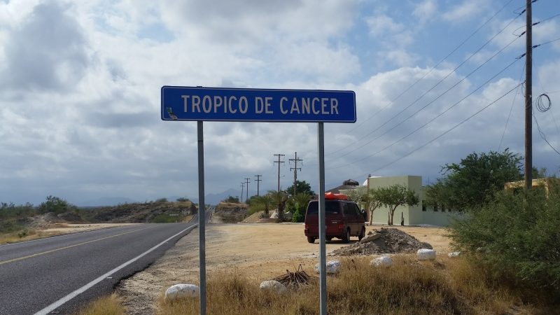 A blue and white Tropic of Cancer road sign in Baja Sur with maroon Volkswagen van in background.