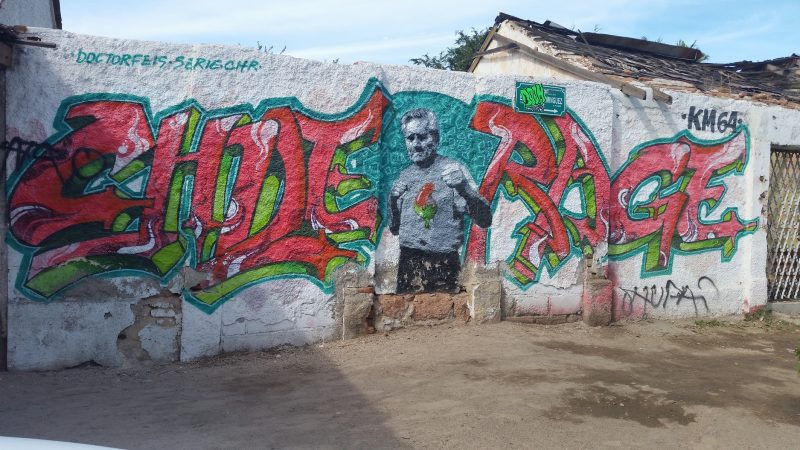 A painting of an old man boxing with a chile pepper for a heart - an example of street art in La Paz, Baja California Sur, Mexico.