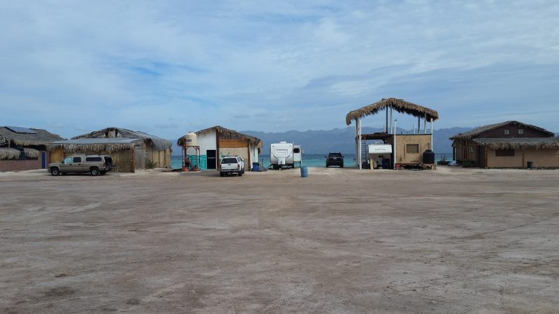 Several beach palapas sheltering trucks and RVs which are Baja California camping for the season.