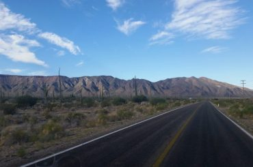 A paved road in Baja California with desert scenery and mountains in the background.