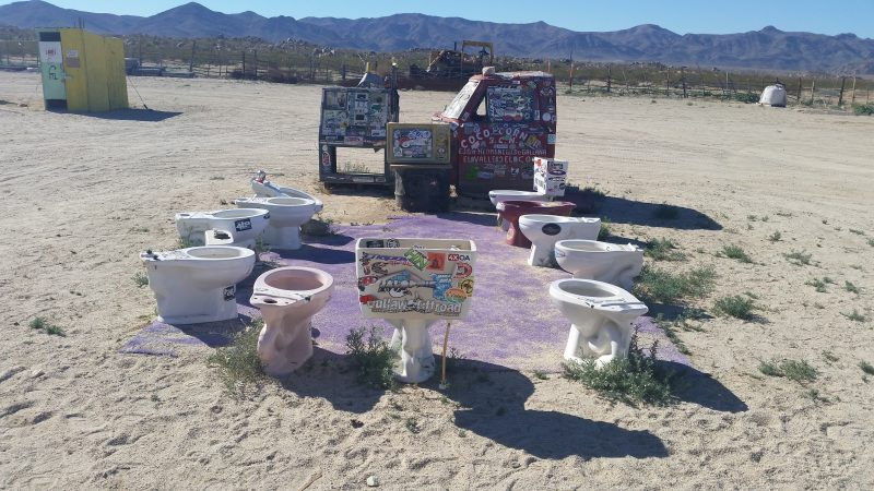 old discarded toilet pots and an old truck covered in stickers in the desert - an iconic site on a Baja California road trip