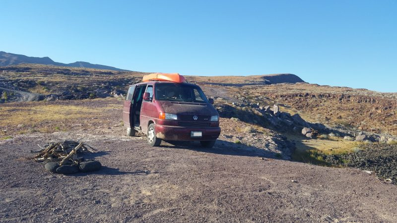 A maroon Volkswagen van with orange kayak on the roof parked on scenic overlook during a Baja California road trip.