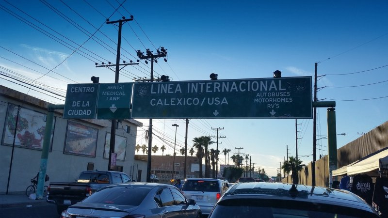 Cars waiting in line to cross from Mexico into the U.S. with a sign above the road.