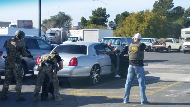 FBI agents with guns drawn on a subject in a grey car.