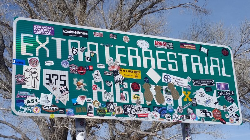 An official green Extraterrestrial Highway sign in Nevada full of many colorful bumper stickers.