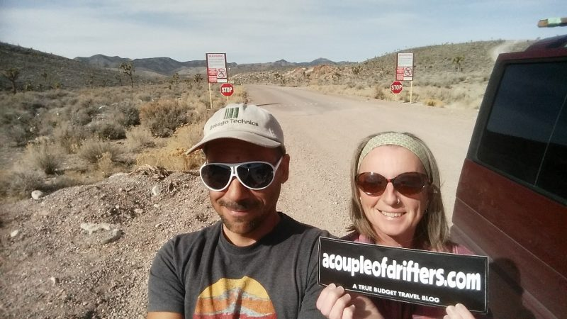 Man and woman holding bumper sticker in front of area 51.