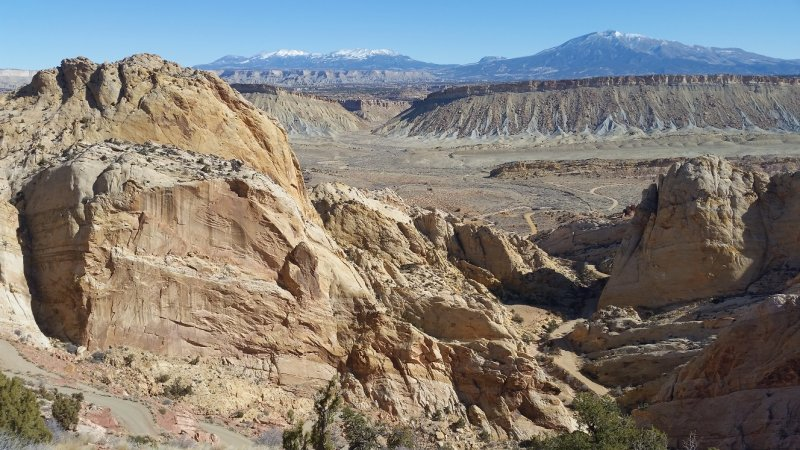A view looking down into a valley at Capitol Reef National Park in the Southwest of the United States with snowy mountains beyond.
