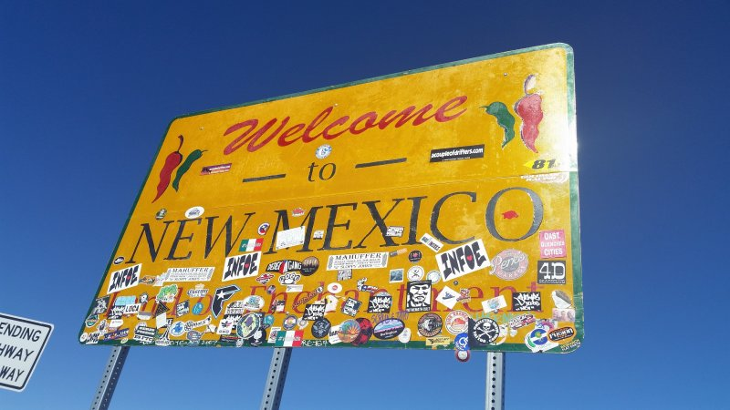 Yellow welcome to New Mexico road sign with stickers on it.