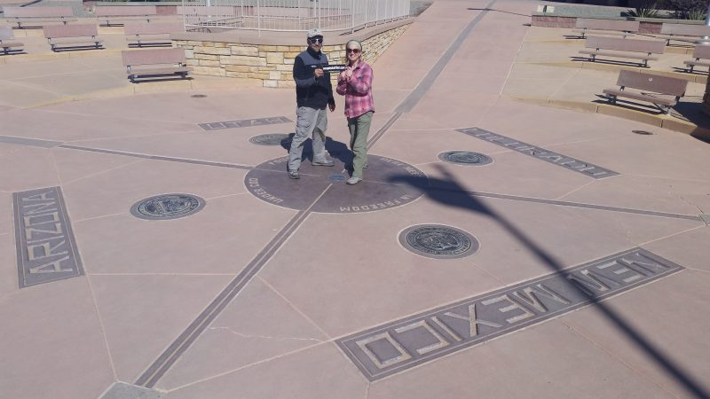 A man and woman on a New Mexico road trip standing on the Four Corners Monument holding a bumper sticker.
