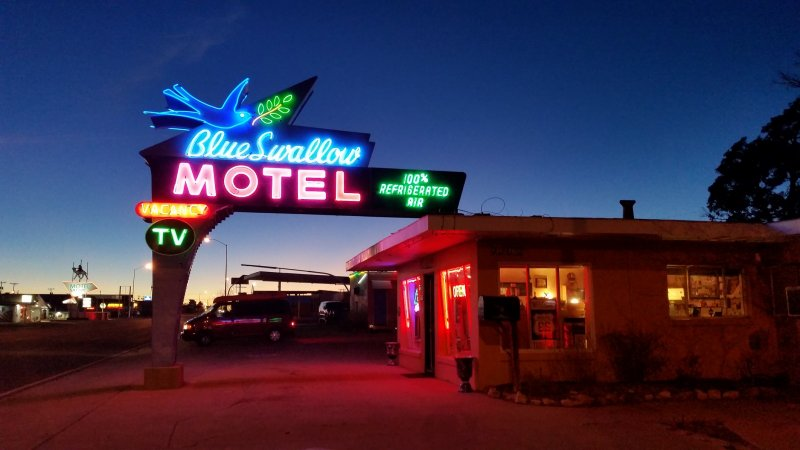 glowing neon sign for the blue swallow motel on route 66 in tucumcari, new mexico.