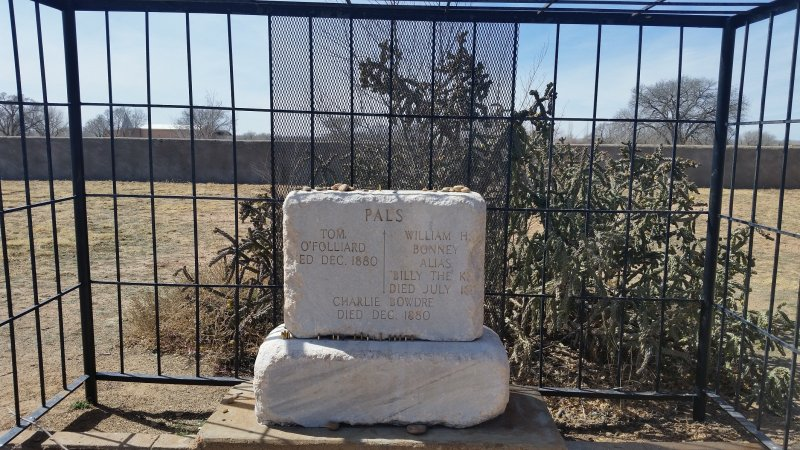 a cage surrounding the grave of billy the kid.