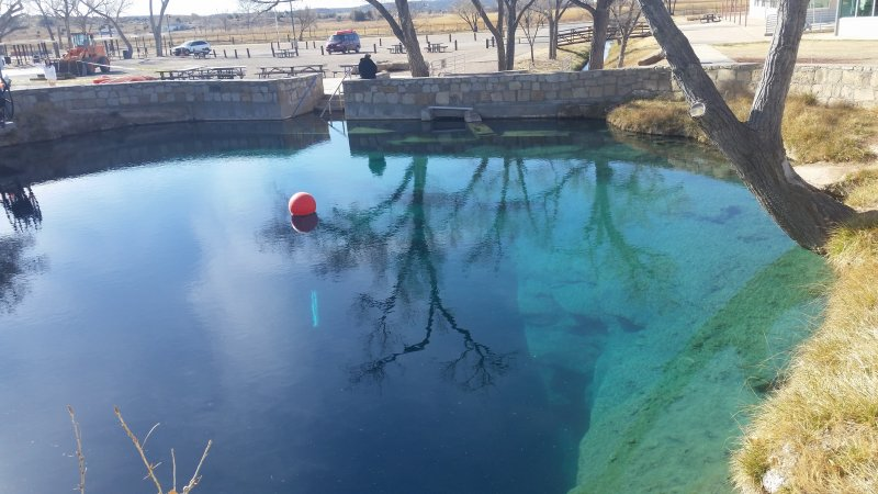 A sinkhole filled with clear blue water.