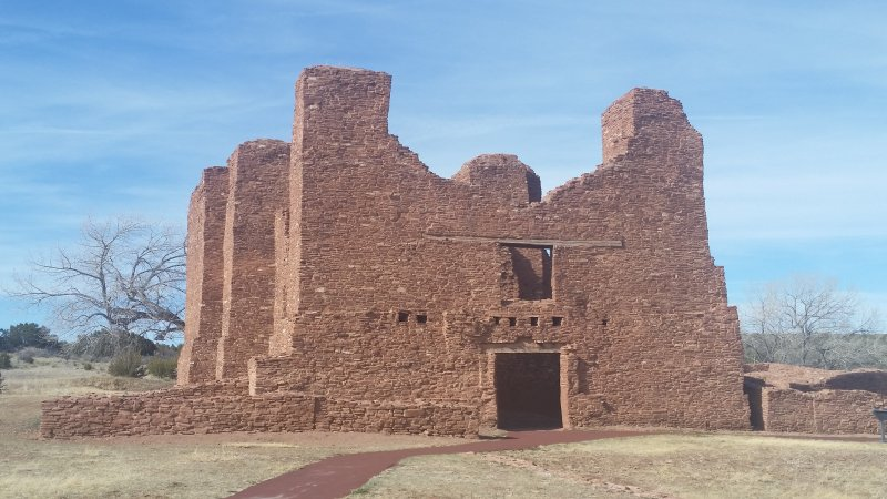 A large ruined red-stone church against a blue sky Quarai, New Mexico