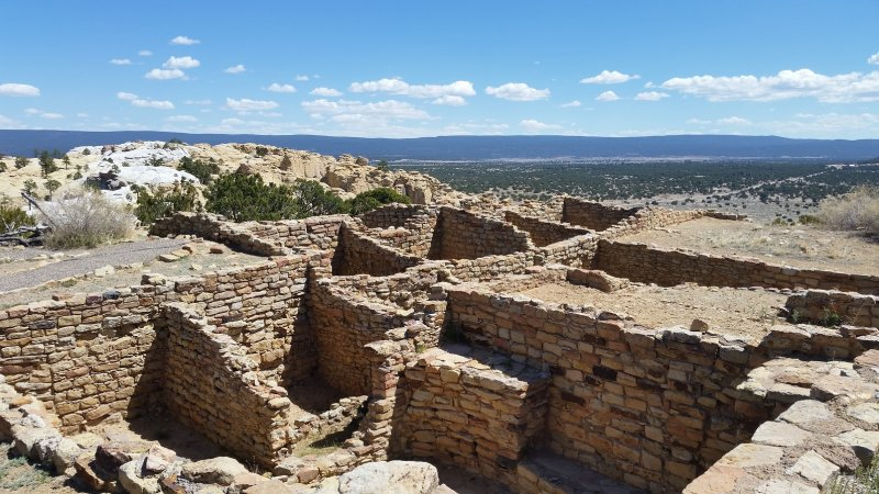 Puebloan stone ruins with mountains in the background at El Morro National Monument, New Mexico.