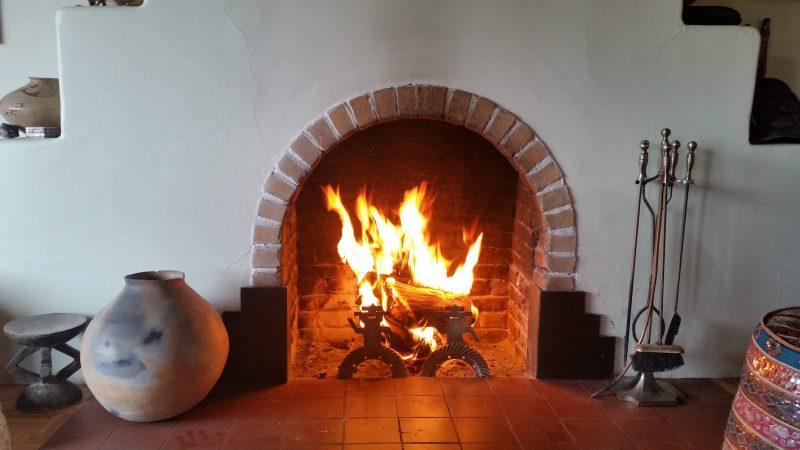 An adobe fireplace with a blazing fire inside of it.
