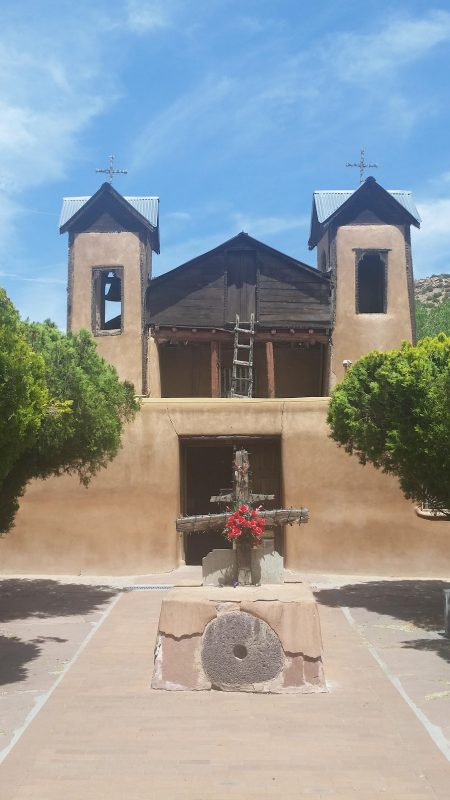 old adobe church with 2 tress in front along the high road to Taos from Santa Fe.