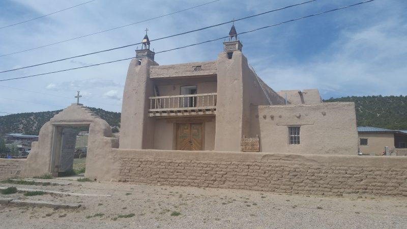 An adobe church surrounded by an adobe wall along the high road to Taos from Santa Fe.