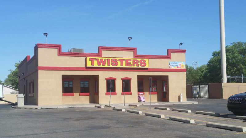 Beige one-storey building with red piping detail and a yellow and red sign advertising a Twisters restaurant on Isleta Blvd. in Albuquerque, New Mexico.