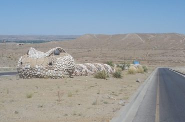 Sculpture of a rattlesnake in the median of a deserted road in the desert.