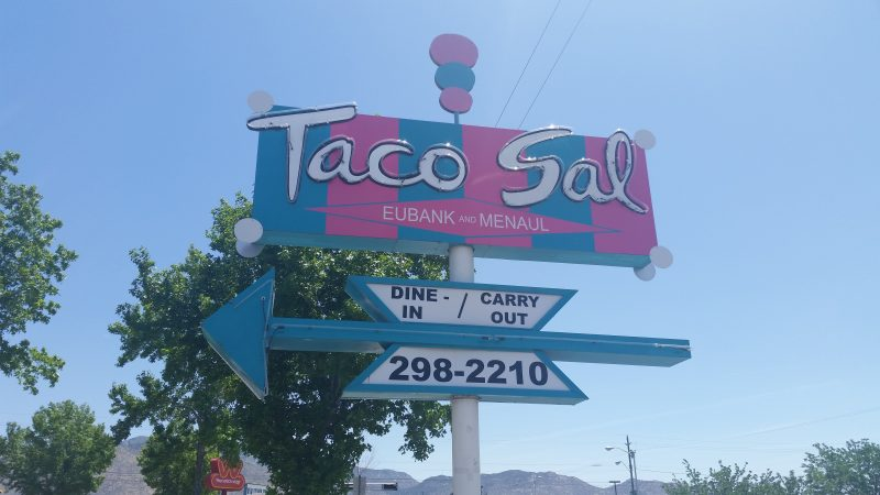 A pink and blue vintage googie-style neon sign advertising Taco Sal, one of the classic places serving tacos and New Mexican food in Albuquerque.