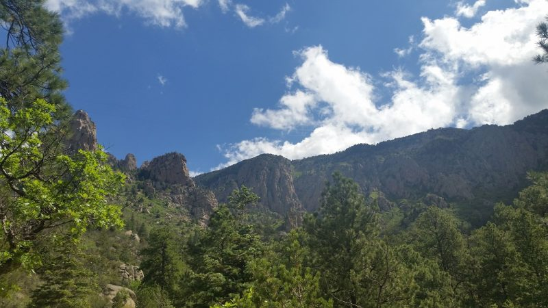 West slope of the Sandia Mountains against a blue sky with a few clouds.