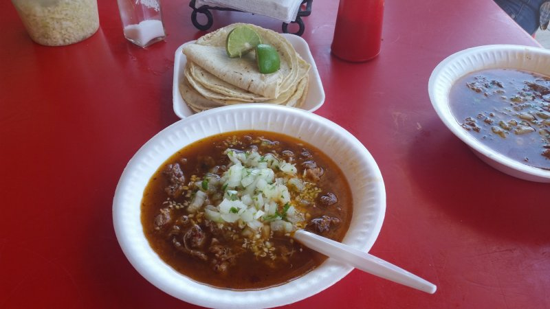 Two white bowls filled with birria and a plate of corn tortillas with lime in Mexico.
