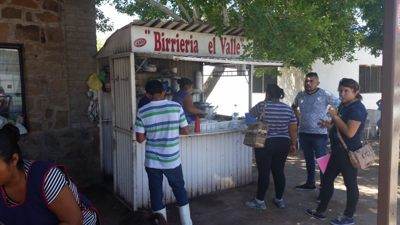 Customers in front of a birria stand ordering food in Loreto, Mexico.