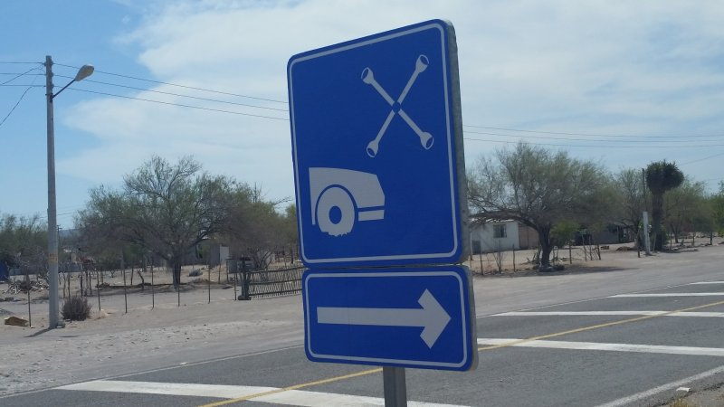 Blue road sign advertising a tire repair shop in Baja Mexico.