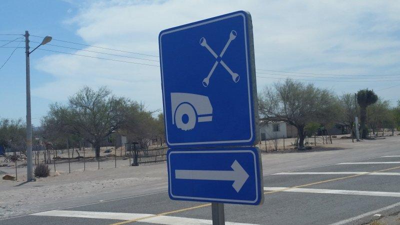 A blue road sign advertising a tire repair shop in Baja California.