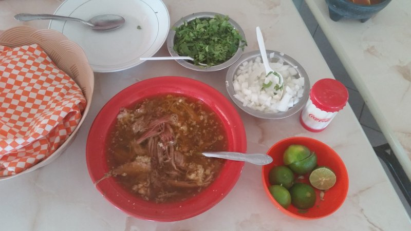 Bowls of onion, cilantro, limes and birria stew in Baja Mexico.