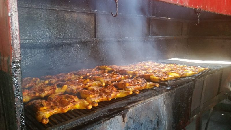 Chickens being grilled over charcoal on the street in Mexico.
