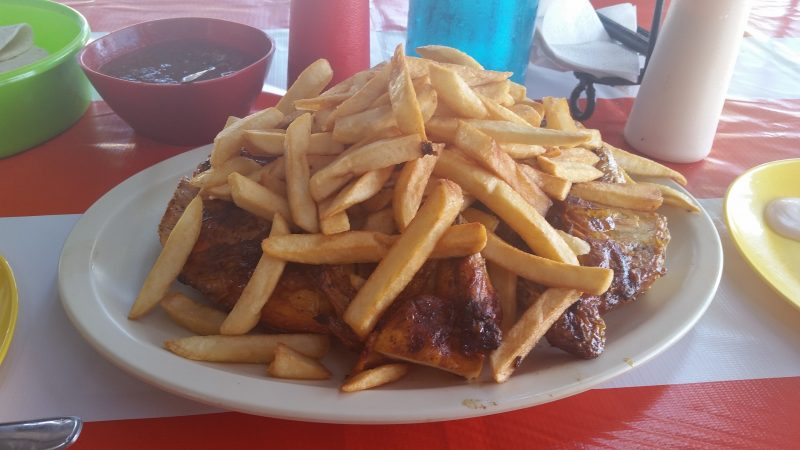 A plate of roast chicken covered in french fries in Mexico.