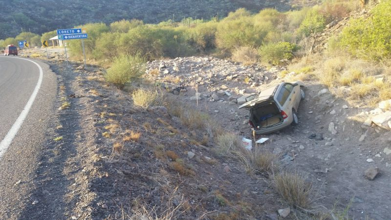 A gold-colored vehicle in a culvert which has gone off the road while driving down the Baja Peninsula Highway.
