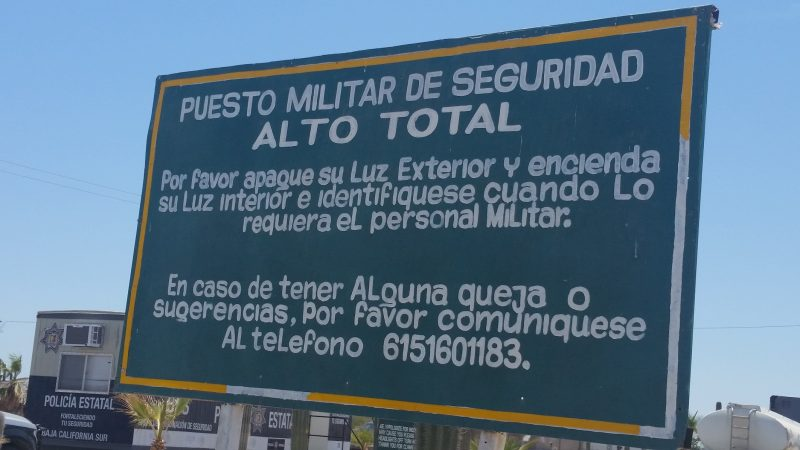 A military checkpoint sign on the side of the highway in Mexico.
