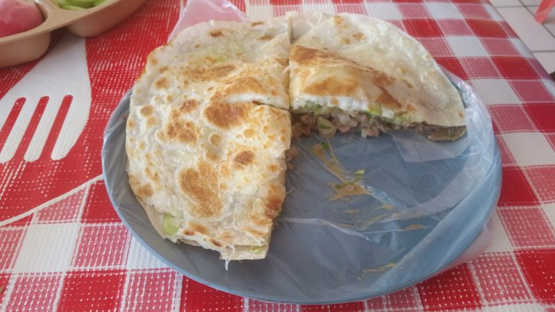 A mulita filled with beef and cheese on a plate in Mexico.