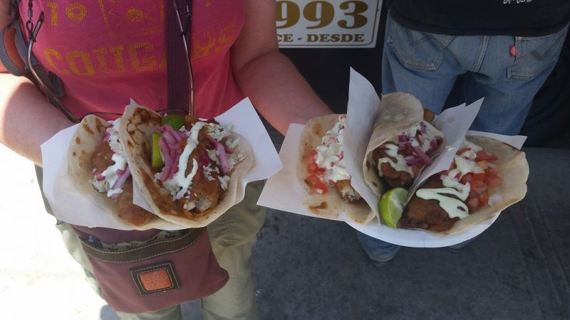 A woman holding two plates, each with two fish tacos topped with slaw, mayonnaise and red onions.