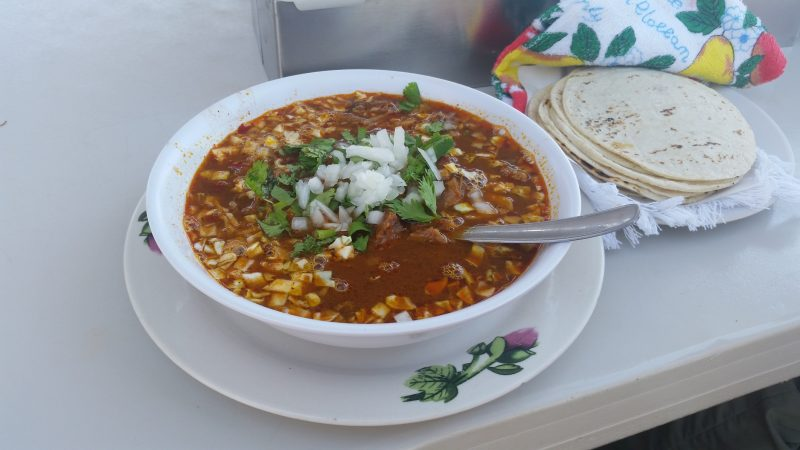A bowl of birria stew with onion, cilantro and corn tortillas on the Baja Peninsula in Mexico.