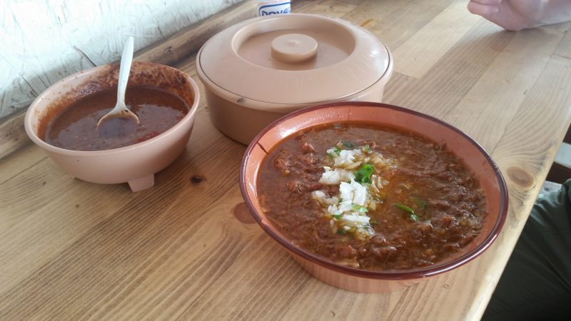 A wooded counter top with a bowl of birria, salsa and corn tortillas in Mexico.