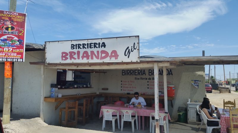 An outdoor birria stand with a few customers in Guerrero Negro, Mexico.