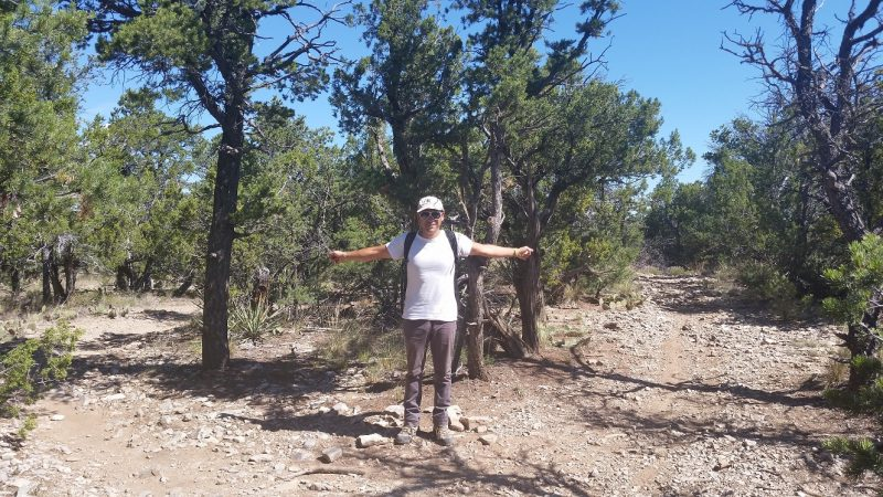 Man pointing toward two different trails while hiking in Albuquerque.