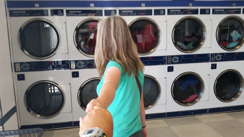 Woman in green T shirt leading man by the hand to washing machines in a laundromat.