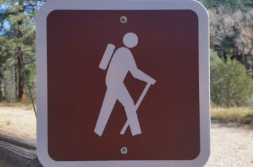 A brown recreation sign of a white figure with a pack hiking.