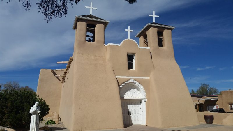 an adobe church with a white door against a blue sky