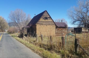 An old adobe house next to a road.