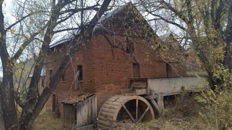 An old adobe mill building with water wheel surrounded by autumn trees.