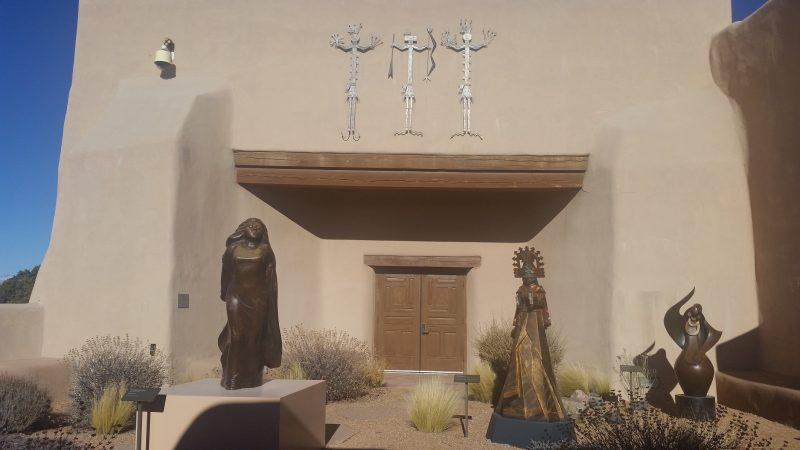 Three bronze statues in front of an adobe building.